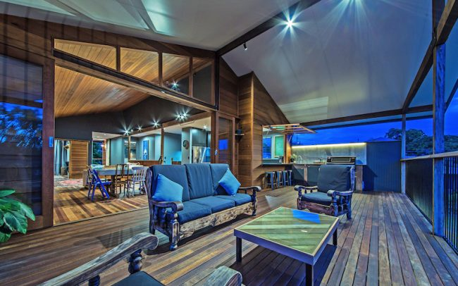 Evening photograph of a rear deck of a Queenslander showing chunky wooden furniture and Eden Made Beautiful Timber fixed triangular windows, stacking doors and large awning kitchen windows, providing each access to the BBE